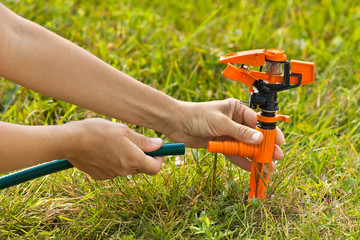 hands installing sprinkler for lawn irrigation