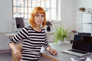 konzentrierte mitarbeiterin in einem modernen büro arbeitet am laptop
