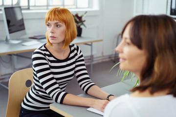 zwei kollegen hören zu in einer besprechung im büro