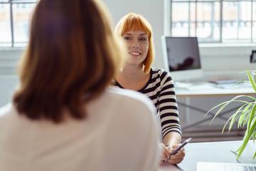 zwei frauen sitzen sich im büro gegenüber in einer besprechung