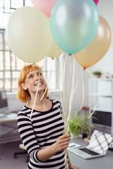 frau im büro freut sich über luftballons