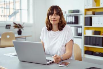 frau arbeitet im büro am laptop