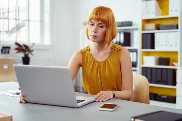 frau sitzt im büro und schreibt konzentriert am laptop