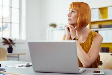 junge geschäftsfrau sitzt am notbook und schaut konzentriert zum fenster