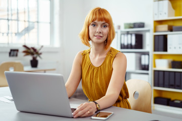 attraktive frau arbeitet im büro am laptop