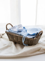 close up of baby clothes for newborn boy in basket