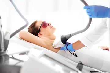 Fototapeta Depilacja laserowa pach. Kobieta na zabiegu depilacji laserowej obraz