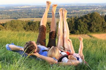 Familie in Tracht liegt im Gras Fuesse hoch