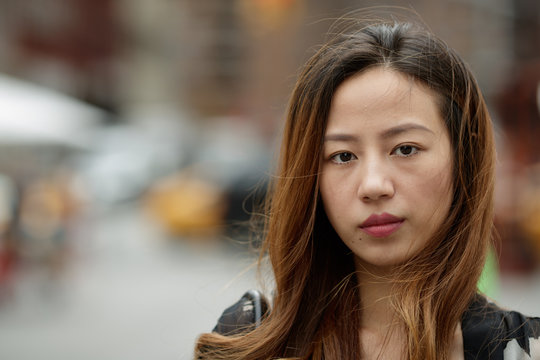 Young Asian woman in city serious face portrait