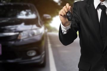 businessman showing a car key - car sale & rental business conce