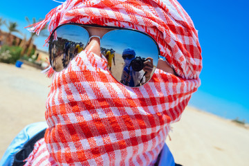 Close up of a man wearing keffiyeh & reflective sunglasses in the Sahara Desert with reflection of the photographer in the lens