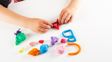 Child hands with colorful clay. Mold letters