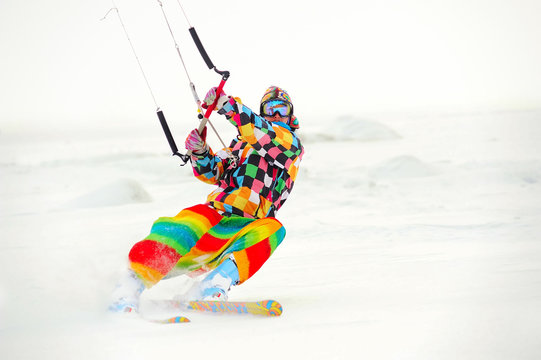 A man in bright colorful clothes is riding a snowkite on the background of snow