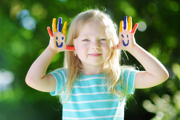 Adorable little girl with her hands painted having fun outdoors