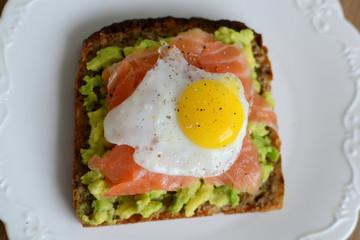 Sandwich with avocado, smoked salmon and quail egg