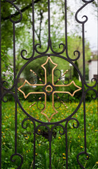 Intricate wrought iron church gate with golden cross on green background