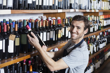 Smiling Salesman Arranging Wine Bottle On Shelf