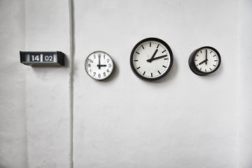 Clocks on a white wall, time passing concept, space for text.