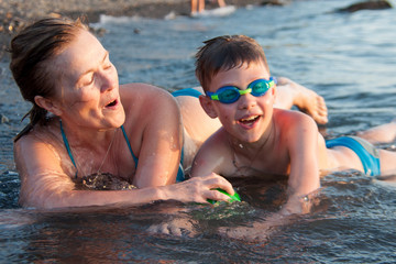 grandmother with her grandson bathing in the sea