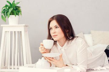 beautiful young woman hold cup of coffee lying think relaxing on the bed, bed home indoors, happy smile day dreaming with tea mug in hands looking up away in thought