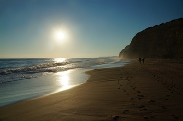 A couple strolls along the water's edge at high tide leaving two lines of foot prints leading down the beach. The sun is reflected on the water and on the wet sand. Algarve, Portugal.