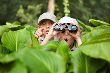 excited young campers hiding in grass looking through binoculars
