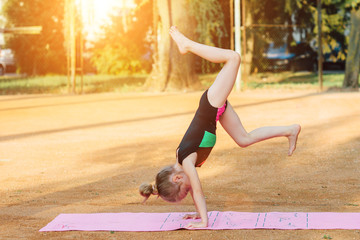 Girl performs gymnastic exercise in the fresh air