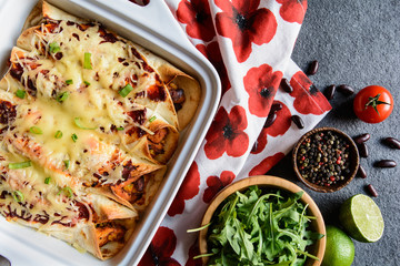Traditional Mexican enchiladas with chicken meat, spicy tomato sauce, corn, beans and cheese