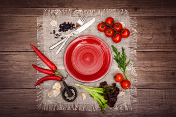 Fresh tomatoes, chili pepper and other spices and herbs around modern red plate in the center of wooden table and cloth napkin. Top view. Blank place for your text. Horizontal.