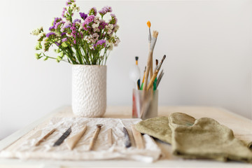 Set of dirty art and craft sculpting tools on wooden table in pottery workshop.Handmade create Concept. flowers on the table, gloves. concept. brush