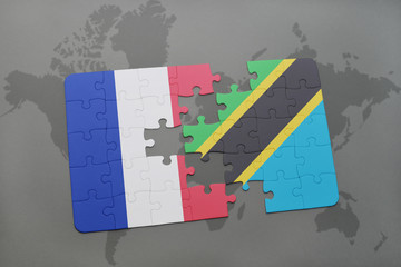puzzle with the national flag of france and tanzania on a world map background.