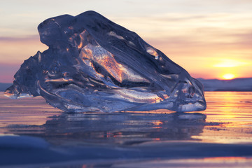 A piece of ice lying on the frozen surface of lake Baikal at daw