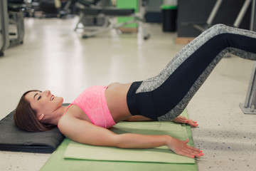 Young woman at the gym lying down
