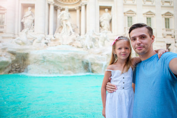 Young father and little girl making selfie in Coliseum, Rome, Italy. Family portrait at famous places in Europe