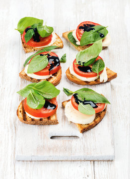 Caprese sandwiches with tomato, mozzarella cheese, basil and balsamic glaze on white painted board over light wooden background, selective focus, vertical composition