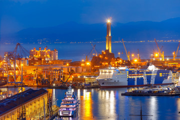 Historical Lanterna old Lighthouse, container and passenger terminals in seaport of Genoa on Mediterranean Sea, at night, Italy.