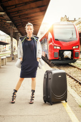 Elegant woman with suitcase posing on the railway station