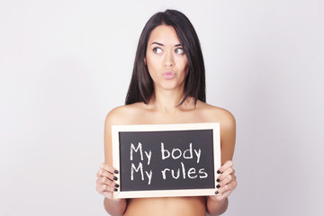 Young woman holding chalkboard saying My body, My rules