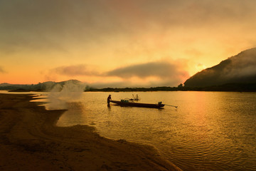 The siluate  fisherman casting a boat in river on during sunset,Thailand