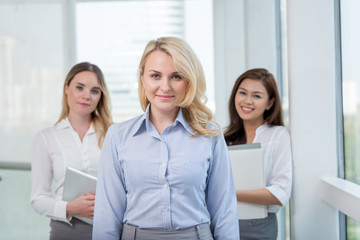 Portrait of female team leader standing in front of her colleagues