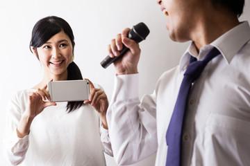 カラオケで歌う男と写真を撮る女性