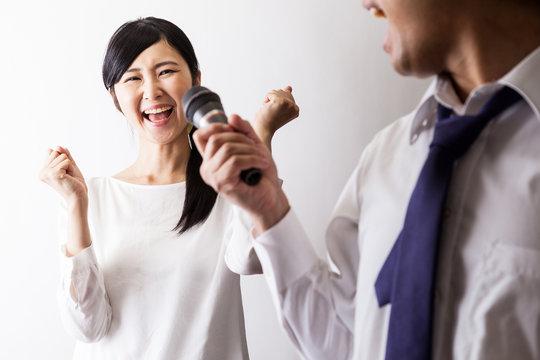 カラオケで歌う男と一緒に楽しむ女性