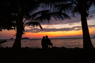 Couple silhouette cuddling and watching sun at sunset on the bea