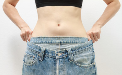 Young woman delighted with her dieting results on white backgrou
