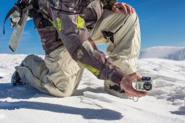 a man filming with action camera in snowy mountain range