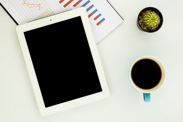 White office workspace with blank screen tablet, chart or graph over backboard and cup of coffee. Top view with copy space