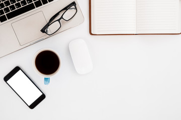 White office workspace with blank screen smartphone, eyeglasses, mouse, laptop, leather notebook and cup of coffee.  Top view with copy space