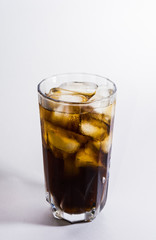 A glass of cold drink with ice on a white background