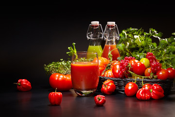 fresh organic tomatoes and tomato juice on black. the detox conc