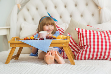 Cute little girl at breakfast on a bed - a focus on a legs